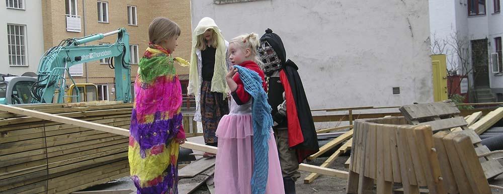 Barna i bakgården planlegger teaterforestilling på byggeplassen.